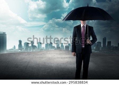 Business man holding umbrella standing on the rooftop of the building
