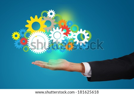 business man holds up a cloud mechanism of gears, concept of ready solutions / manpower / hr / employee - stock photo