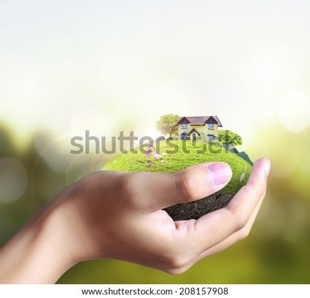 Business man house in human hands  - stock photo