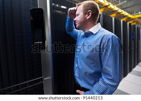 Business man in a data center looking frustrated with the current system. He is looking for a better IT solution.