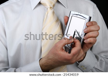 Business man in a suit holding pda and stylus - stock photo