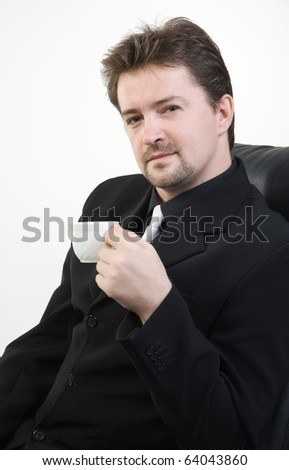 Business man in black suit drinking tea