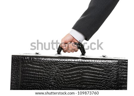 Business man in black suit hand holding large travel luggage suitcase - stock photo