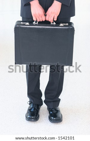 Business man in black suit with black shoes is holding a black briefcase - stock photo