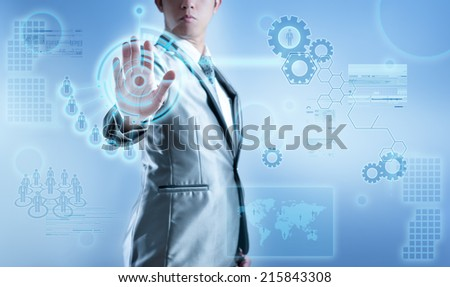 Business man in blue grey suit using hand pressing on digital virtual screen, business concept of marketing strategy plan - stock photo