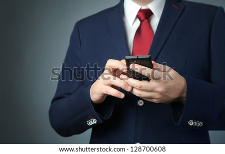 business man in blue suit with mobile phone - stock photo