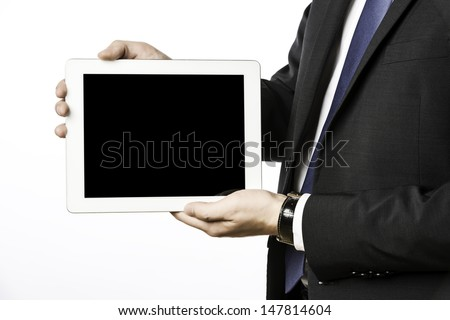 Business man in dark suit with blank tablet computer, isolated on white background
