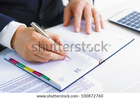 Business man in dark suit writing  in his datebook