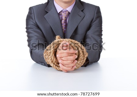 Business man in elegant suit sitting at desk tied hands with rope concept. Isolated over white background.