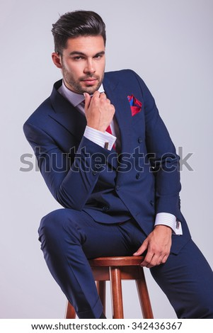 business man in elegant suit sitting in studio while touching his chin
