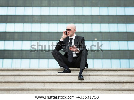 Business man in luxury suit with tablet computer in hand check quotations his shares on international stock exchanges and talking via mobile phone. - stock photo