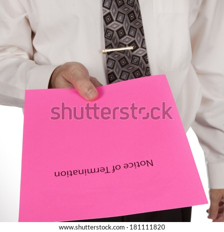 Business man in shirt and tie handing out a notice of termination or pink slip - stock photo