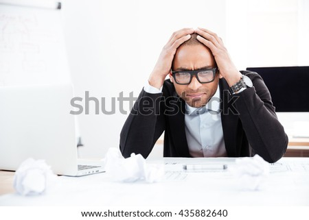 Business man in stress or depression sitting at the desk on office - stock photo