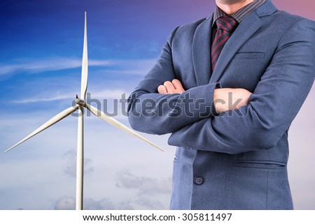 Business man in suit on wind turbine for electricity background