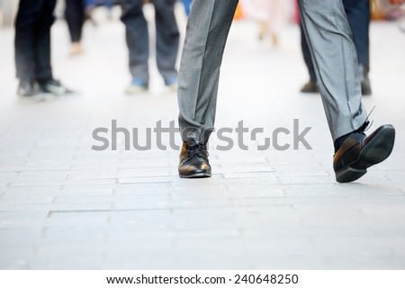 Business man in suit taking a big fast step forward - stock photo