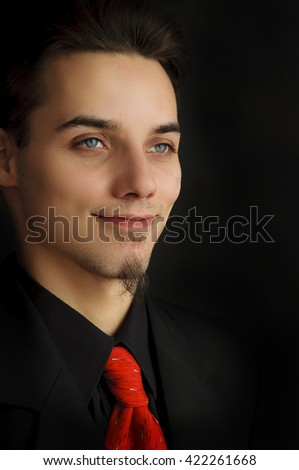 business man in suit with red tie on black background - stock photo