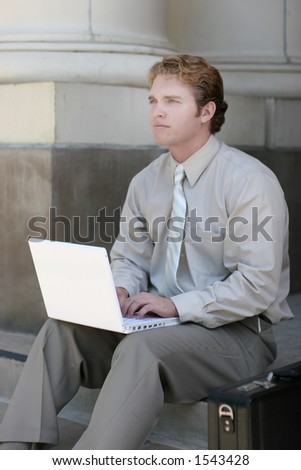 Business man in tan shirt and tie is looking up as his hands are on his white laptop, as he sits on the steps of the courthouse next to his briefcase