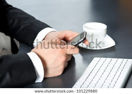 business man in the office drinking coffee and talking on the touch tablet phone gadget. - stock photo