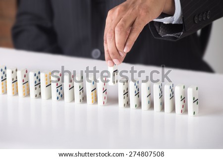 Business man is arranging dominoes in a line. Concept image for business strategy and game plan. Person is wearing a black suit and tie. He is seated in an office room with a white desk.  - stock photo