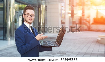 Business man is holding his laptop and shows on the screen.