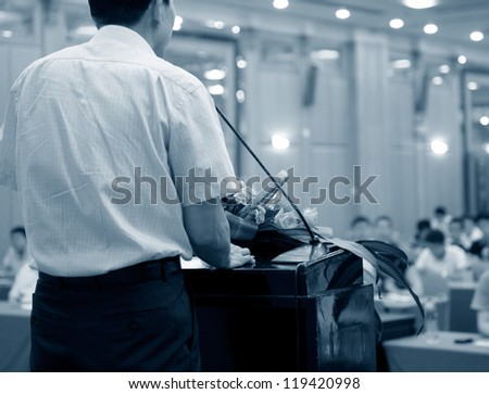 Business man is making a speech in front of a big audience at a conference hall. - stock photo