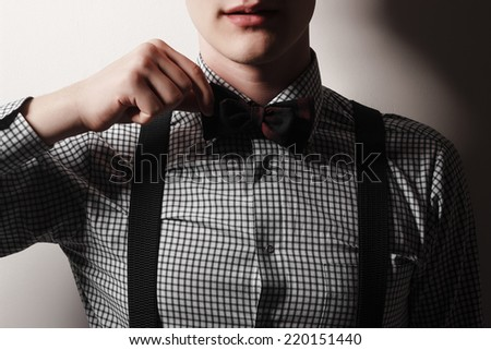 Business man is posing in studio with bow tie and braces on white background. - stock photo