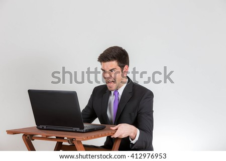 Business man is yelling at a laptop