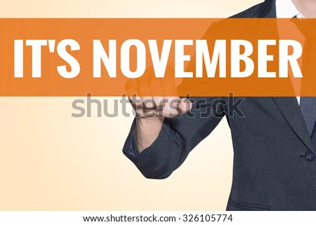 Business man It November word touch on virtual screen orange background - stock photo