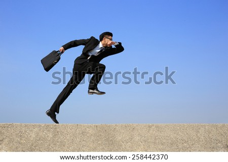 business man jump and run with blue sky background, full length, asian male, slight motion blur - stock photo