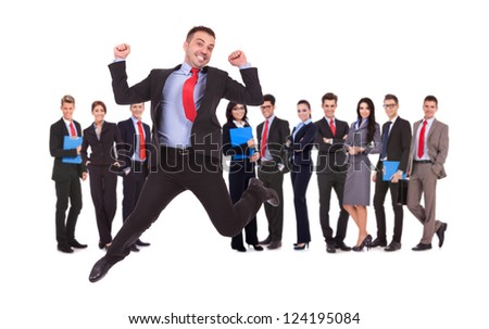 business man jumping in front of his business team formed of young businessmen and businesswomen standing over a white background - stock photo