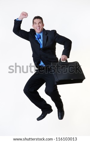 business man jumping in the air with a large smile on his face holding a briefcase