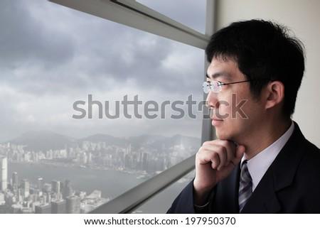 Business man look city and dark storm cloud through window with serious face, asia, hong kong, asian - stock photo