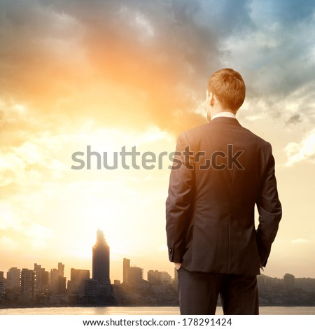 business man look sunrise in the city - stock photo