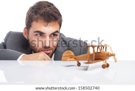 business man looking a wooden airplane on white background - stock photo
