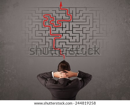 Business man looking at a maze and the way out on brown wall - stock photo