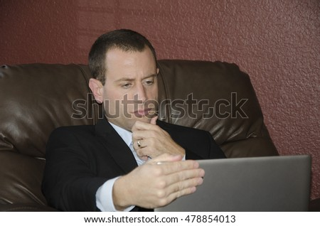 Business man looking at his laptop sitting in his brown leather chair.