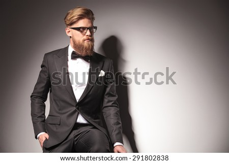 Business man looking away from the camera while sitting with his hand in pocket.