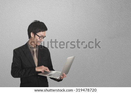 Business man looking laptop and concrete wall background.Copy space.