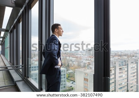 Business man looking out through the office balcony. - stock photo
