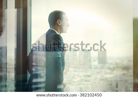 Business man looking out through the office balcony seen through glass doors. Post processed with vintage filter. - stock photo