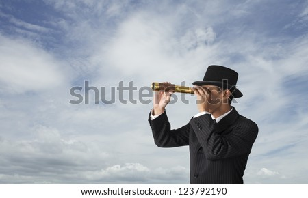 business man looks through a telescope with blue sky - stock photo