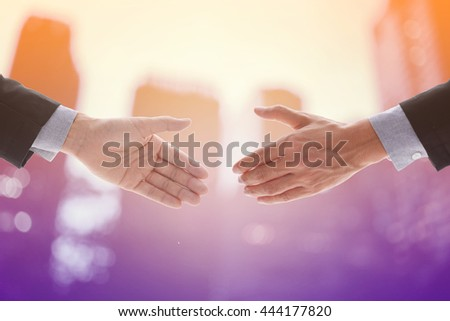 Business man make handshake in agreement with capital or city background, business concept in agreement handshaking, retro filter and vintage style with glow light.  - stock photo