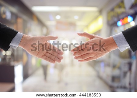 Business man make handshake in agreement with interior of building in capital or city background, business concept in agreement handshaking, retro filter and vintage style with glow light.  - stock photo