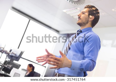 Business man making a presentation at office. Business executive delivering a presentation to his colleagues during meeting or in-house business training. Business and entrepreneurship. - stock photo