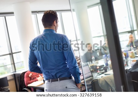 Business man making a presentation at office. Business executive delivering a presentation to his colleagues during meeting or in-house business training. View through glass. - stock photo