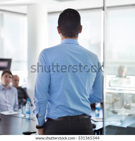 Business man making a presentation at office. Business executive delivering a presentation to his colleagues during meeting or in-house business training. Rear view. Shalow depth of field. - stock photo