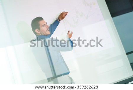 Business man making a presentation in front of whiteboard. Business executive delivering a presentation to his colleagues during meeting or in-house business training. View through glass. - stock photo