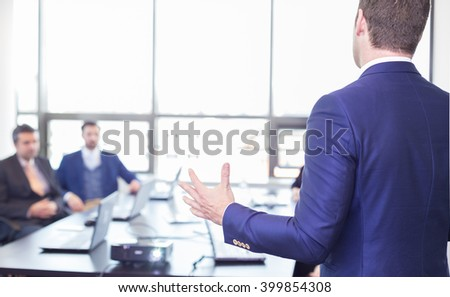 Business man making a presentation in office. Business executive delivering a presentation to his colleagues during meeting or in-house business training, explaining business plans to his employees.  - stock photo