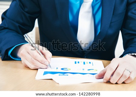 Business man making notes to sales report