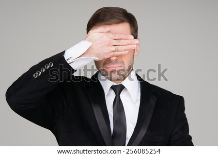 Business man making the see no evil gesture. Businessman covering his eyes with his hand - stock photo